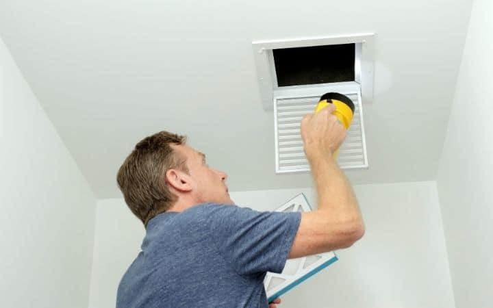 Man checking HVAC ducts