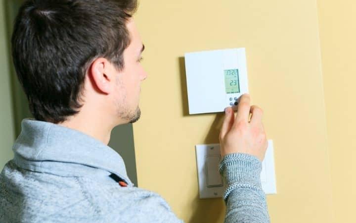 Man handling thermostat